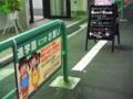 通学路の注意看板と2.7次元行きの看板が同居する街。