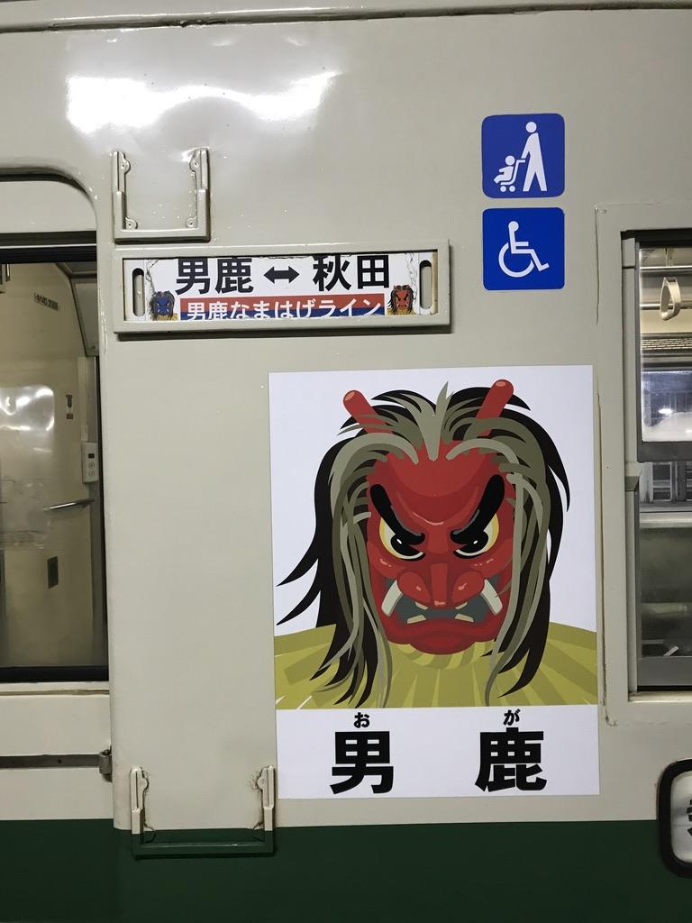 なまはげのイラストと行先表示、ベビーカー・車椅子のアイコンが並べられたキハ40系の側面(2020/1/11@秋田駅)