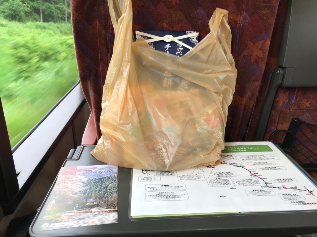 椅子の後ろに置かれていたリゾートみのり号案内と、旅行商品のお菓子類(2019/6/30)