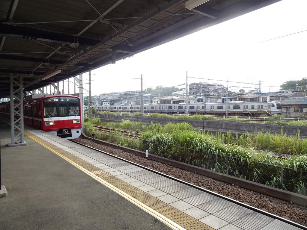 生麦駅に停車中の京急1500形普通品川行きと、横を通るE217系横須賀線(2020/8/10)