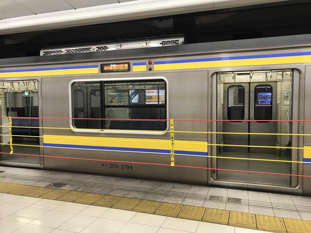 空港第2ビル駅の昇降式ホーム柵が下がり、間もなくドアが閉まる209系成田空港行き(2020/8/23)