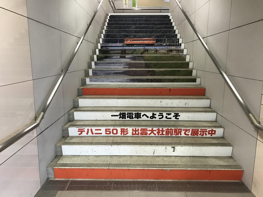電鉄出雲市駅の改札からホームに上がる階段に掲示されているデハニ50形の写真(2020/10/17)