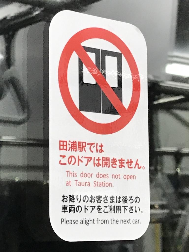 E235系1号車ドアに貼られた、田浦駅でドア開かない掲示(2020/12/21)