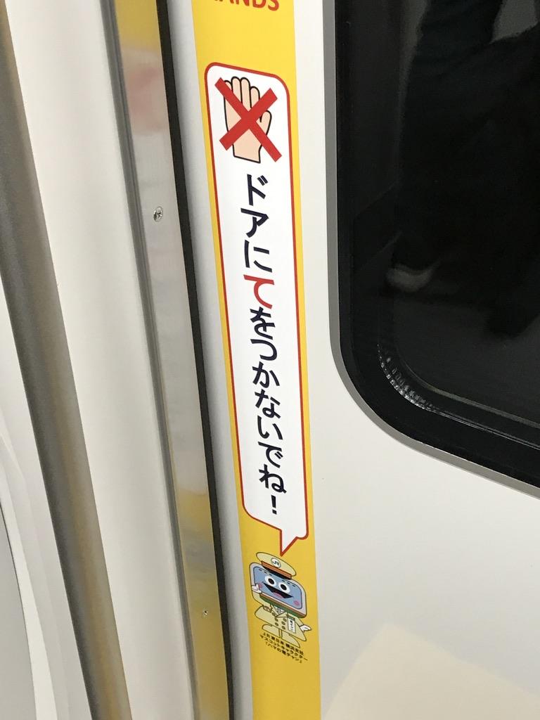 E235系1号車ドアに貼られた、ドアにご注意のシール(2020/12/21)