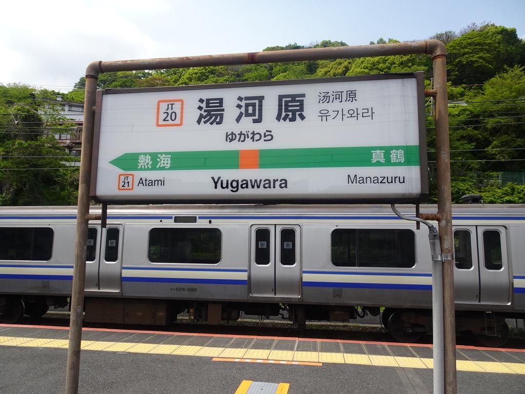 湯河原駅の駅名標と、留置されるE217系(2021/4/25)