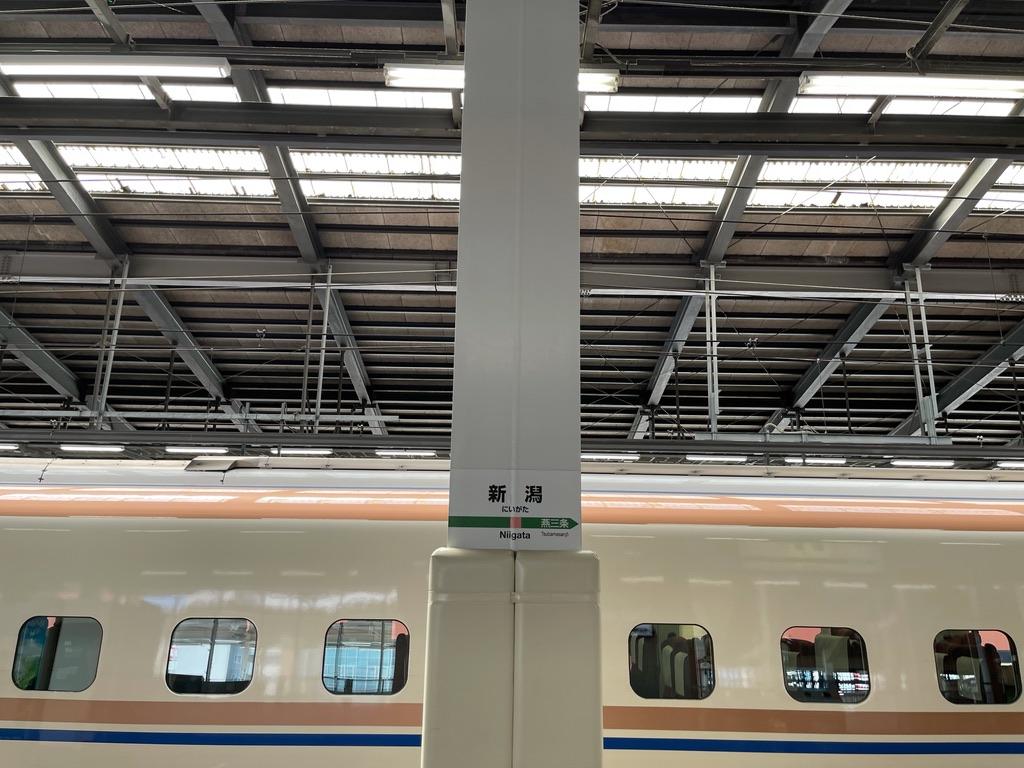 新潟駅12番線に停車中のE7系と、その先に屋根が見える13番線に停車中のE4系