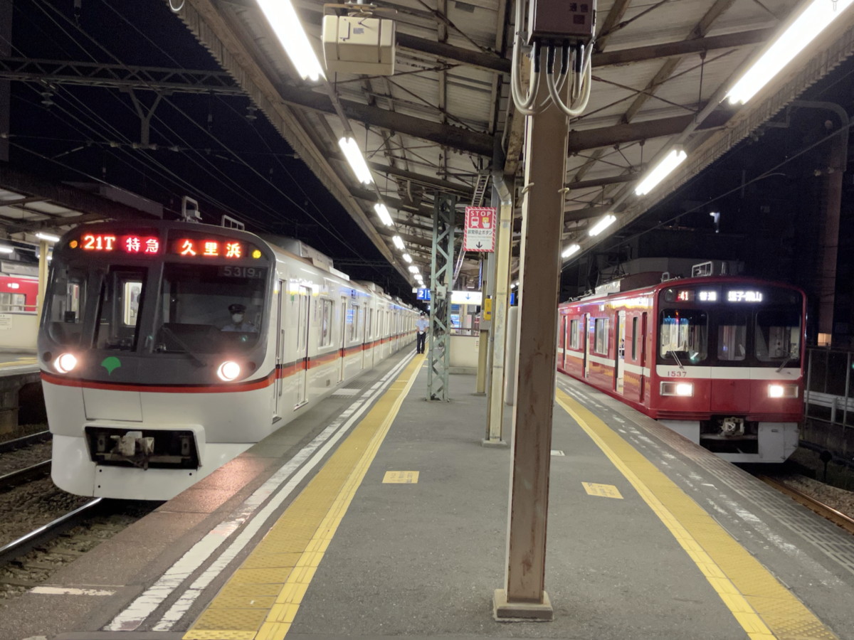 神奈川新町駅2番線に到着する特急京急久里浜行き、1番線で待避中の普通逗子・葉山行き(2021/7/18)