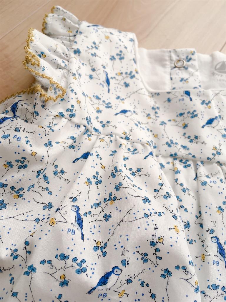 白地に青い小鳥や植物がプリントされたワンピース風トップス