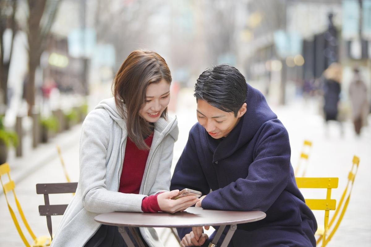 男女のカップルが連絡について話し合っているイメージ。男女が外のカフェテラスで女性のスマホの画面を見ている写真となります。