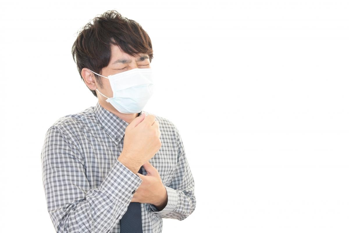 私が風邪を患ったイメージです。マスクを着けて咳をしている若い男性の写真です。