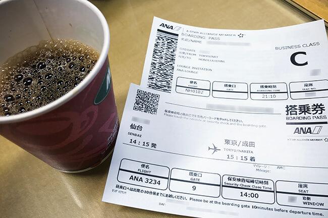 ホノルル行きビジネスクラス搭乗券とコーヒー