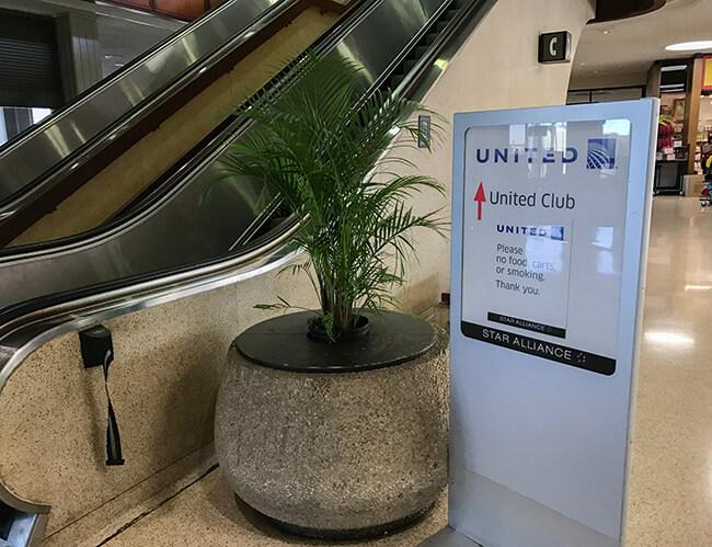 ホノルル空港9番搭乗口を入った場所にあるエスカレーターとユナイテッドクラブの看板