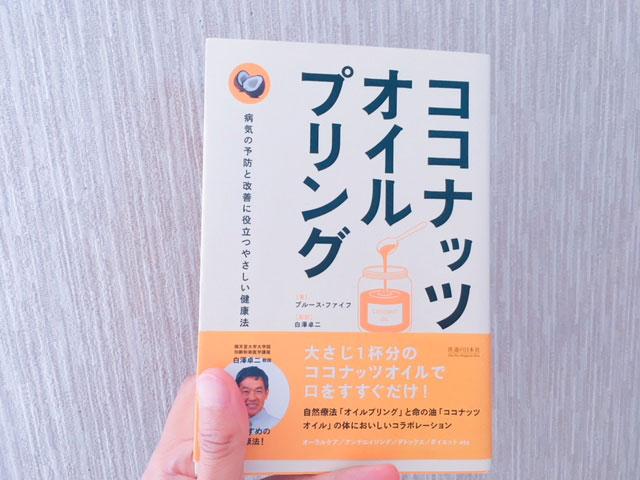 手に持ったココナッツオイルプリングの本