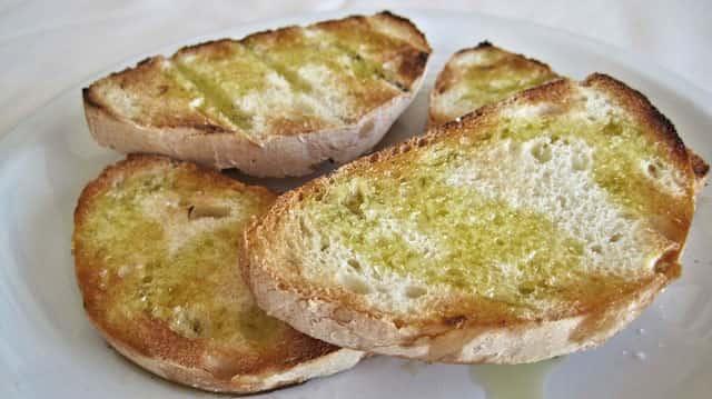 パンにオリーブオイルがかけられている写真