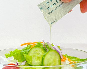携帯用の美容ボタニカルオイルをサラダにかけている写真
