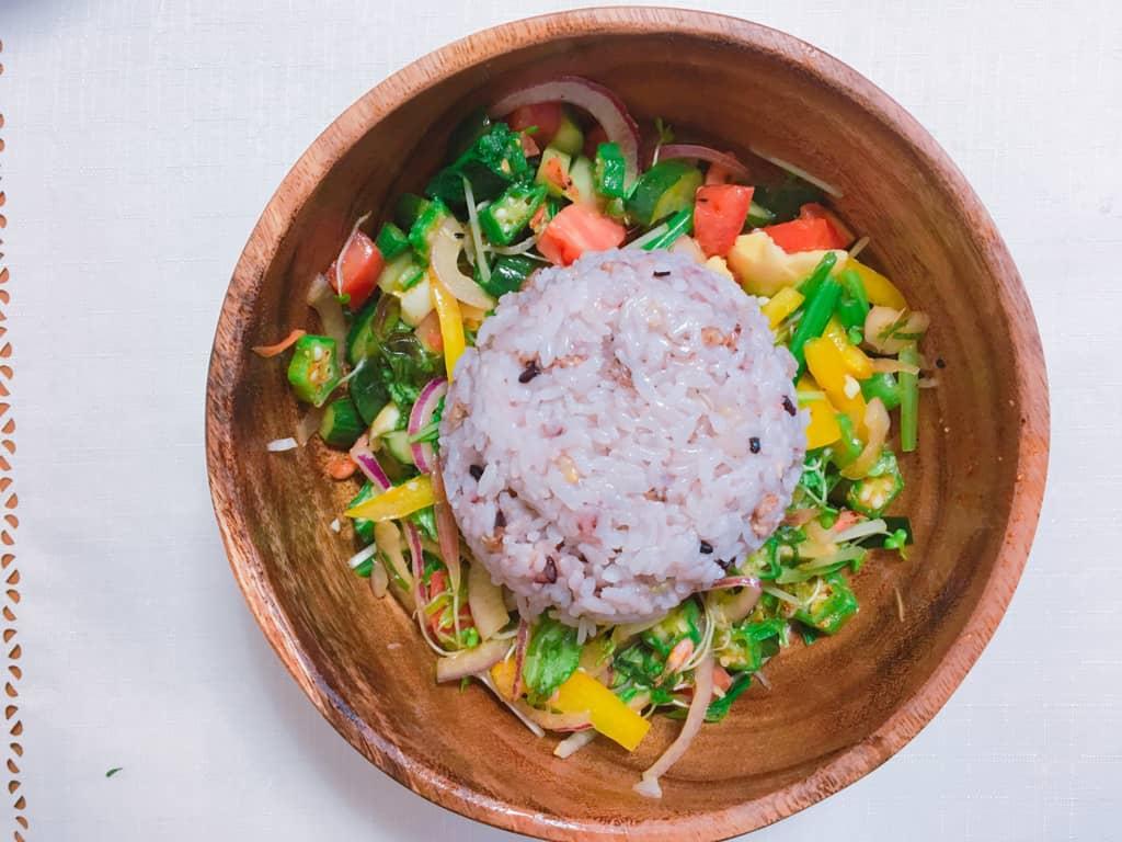 木製サラダボウルに野菜サラダとご飯がもられている写真
