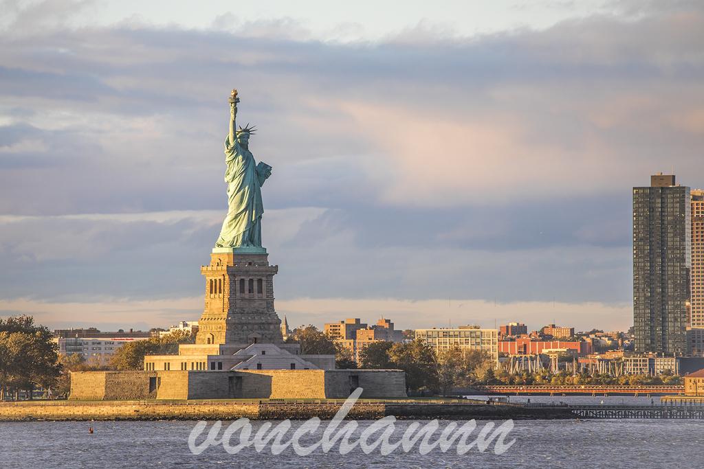 出航後の船から見える、夕日に照らされた自由の女神