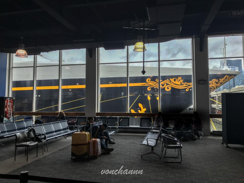 クルーズターミナルで待つ人と窓の奥にあるマジック号