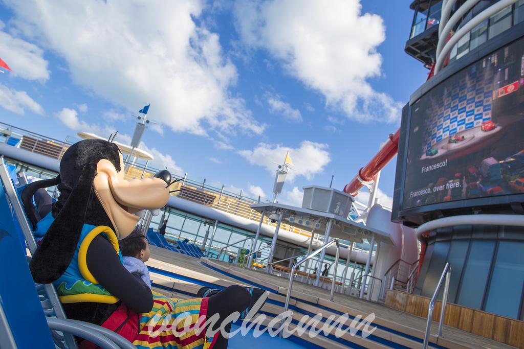 ビーチベッドで「カーズ」を鑑賞する水着グーフィー