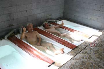 パミール高原の温泉につかる斉藤さん(手前)と石井さん