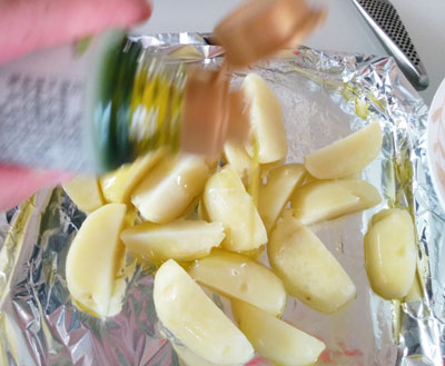 蒸かしたジャガイモにオリーブオイルをまぶす