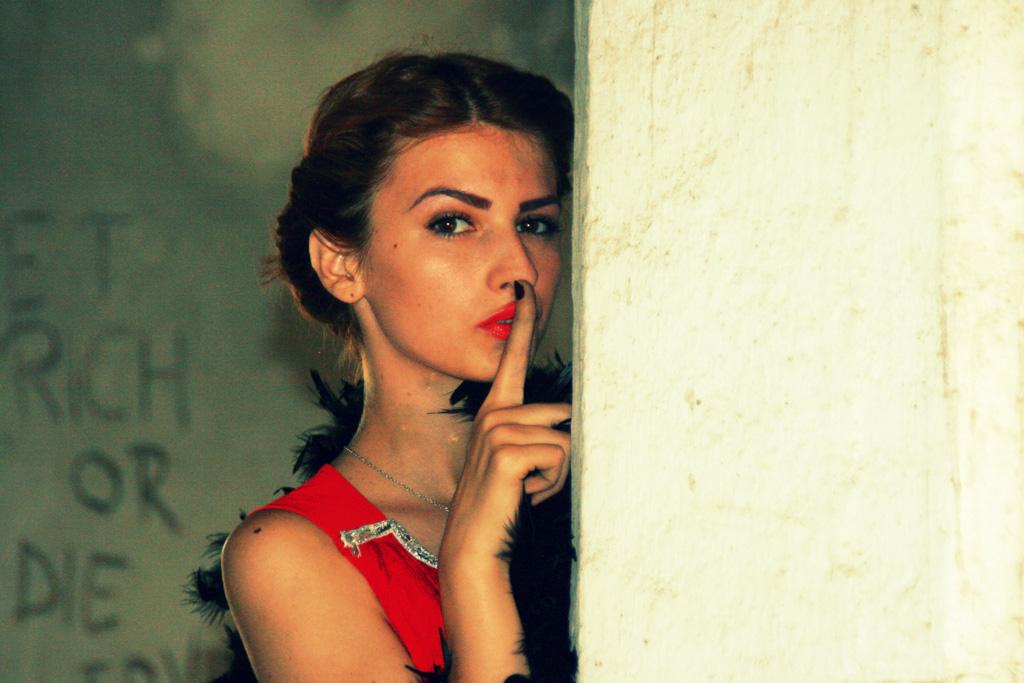 内緒話のポーズをする赤いドレスの外国人女性