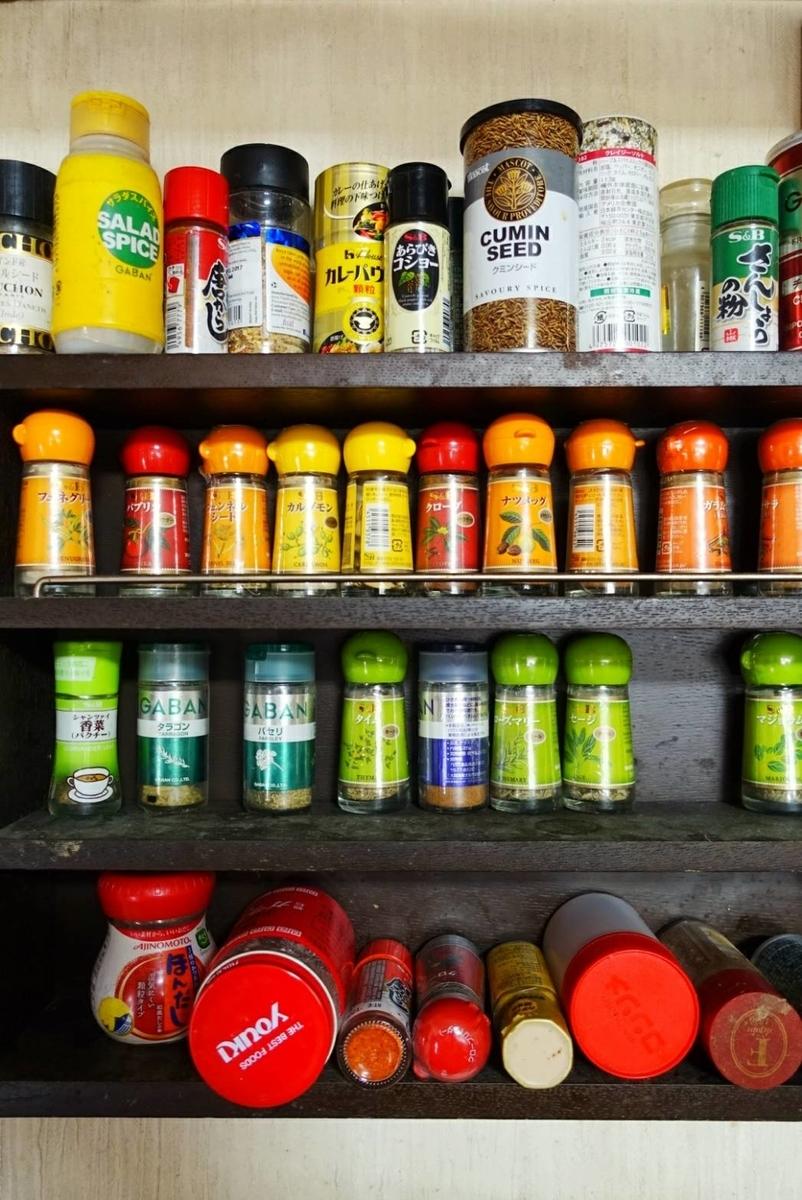 三段の壁取り付け式スパイスラック。棚いっぱいに小瓶が並んでいる。