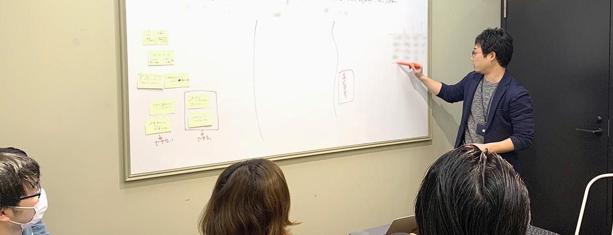 写真:ホワイトボードを書きながら説明する人と、聞き入る人