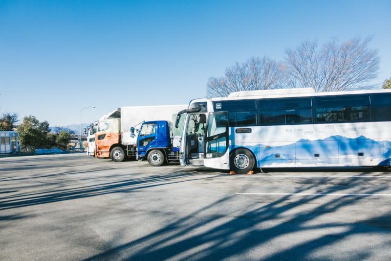 高速のパーキングに停車中のバスと大型トラック