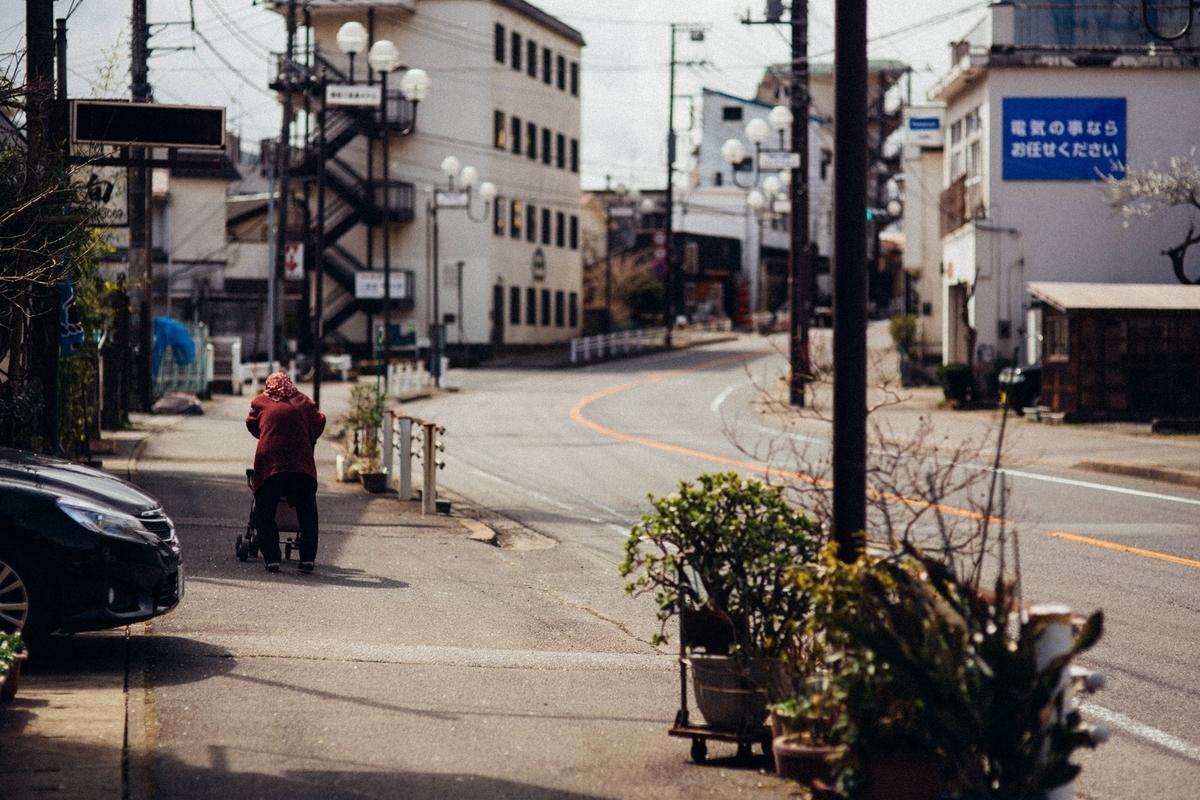 閑散とした街と老婆の後ろ姿のフリー画像(写真)