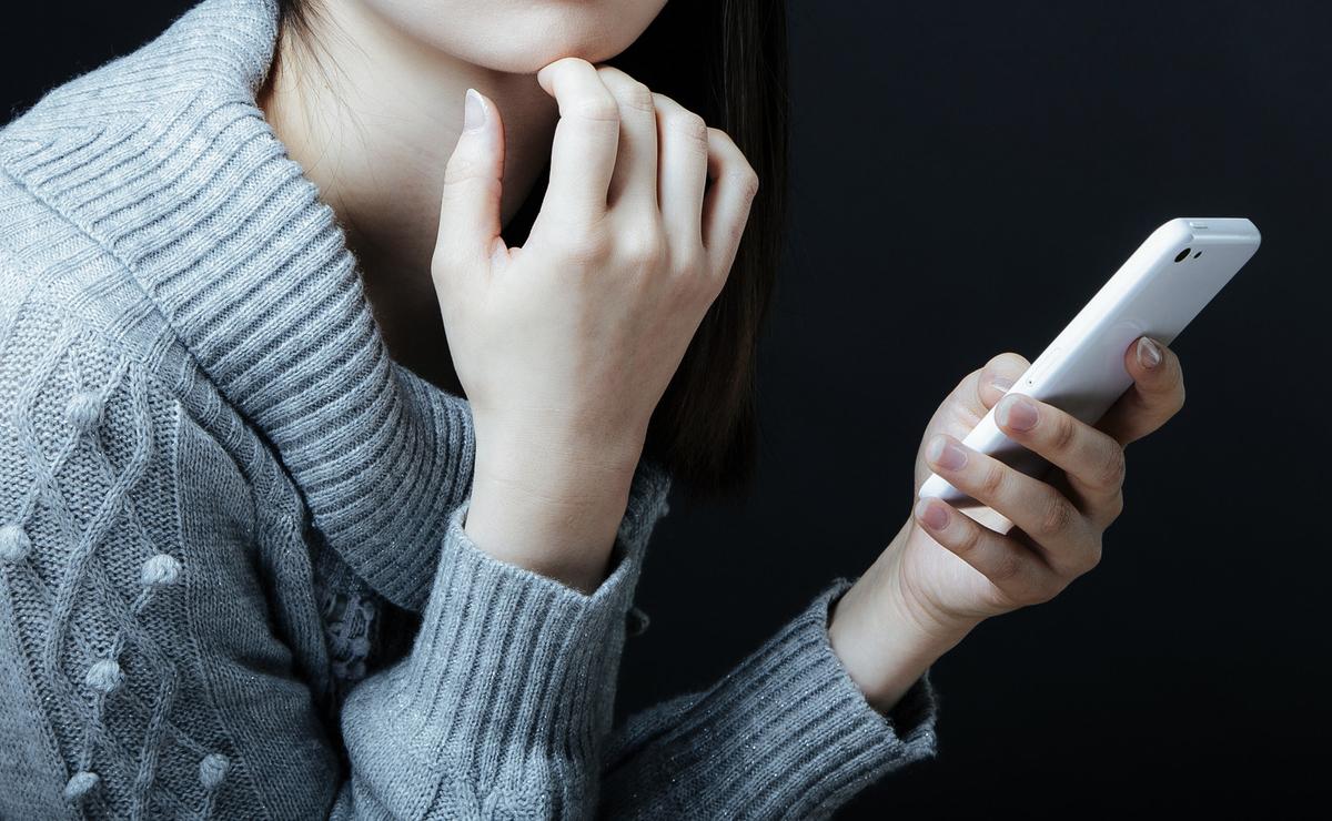 深刻な悩みをネットで相談する女性のフリー画像(写真)