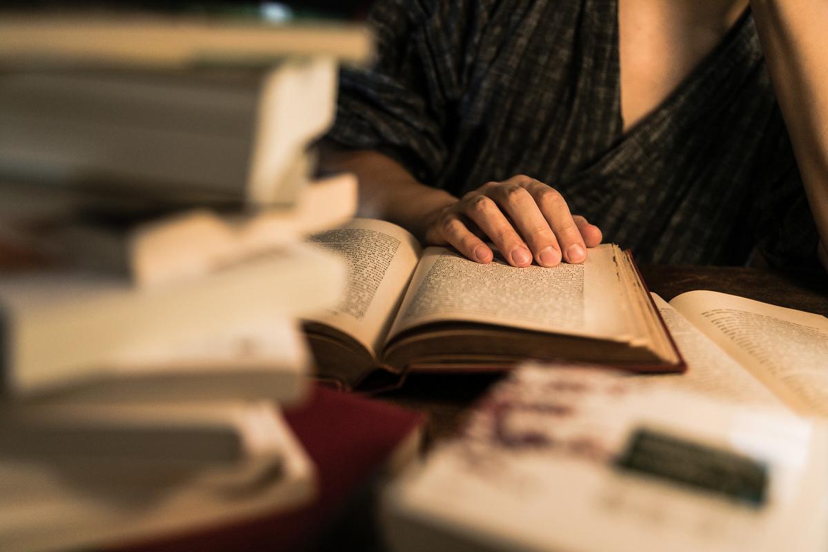 積まれた本と、徹夜で調べものをする様子のフリー画像(写真)