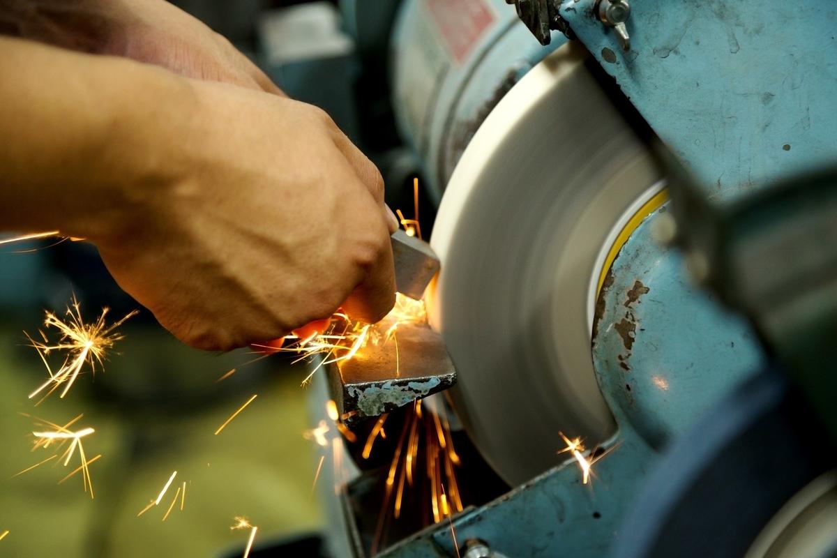 グラインダーを使う職人の手と火花が散る様子のフリー画像(写真)
