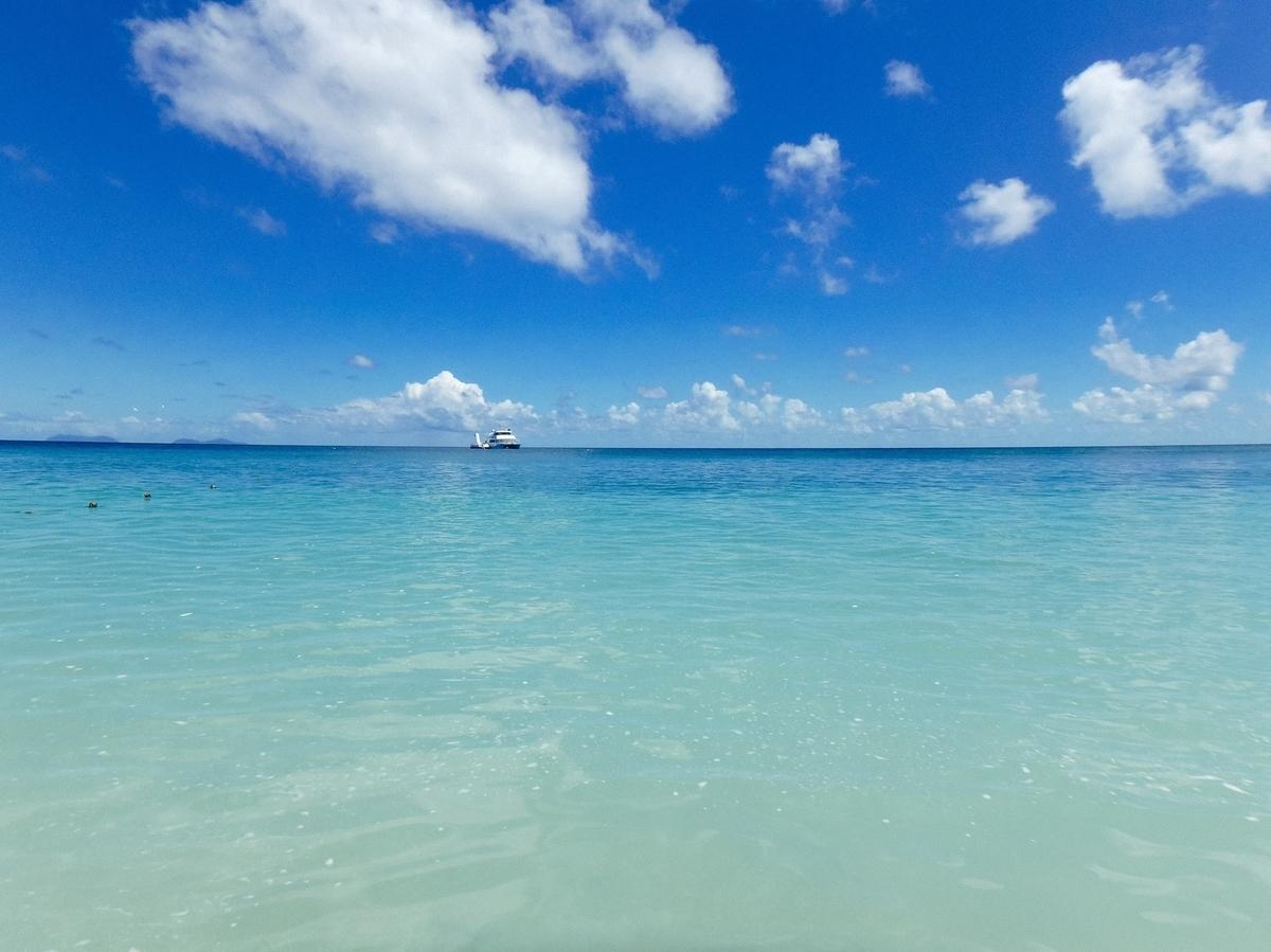 真っ青な海に浮かぶクルーザーのフリー画像(写真)