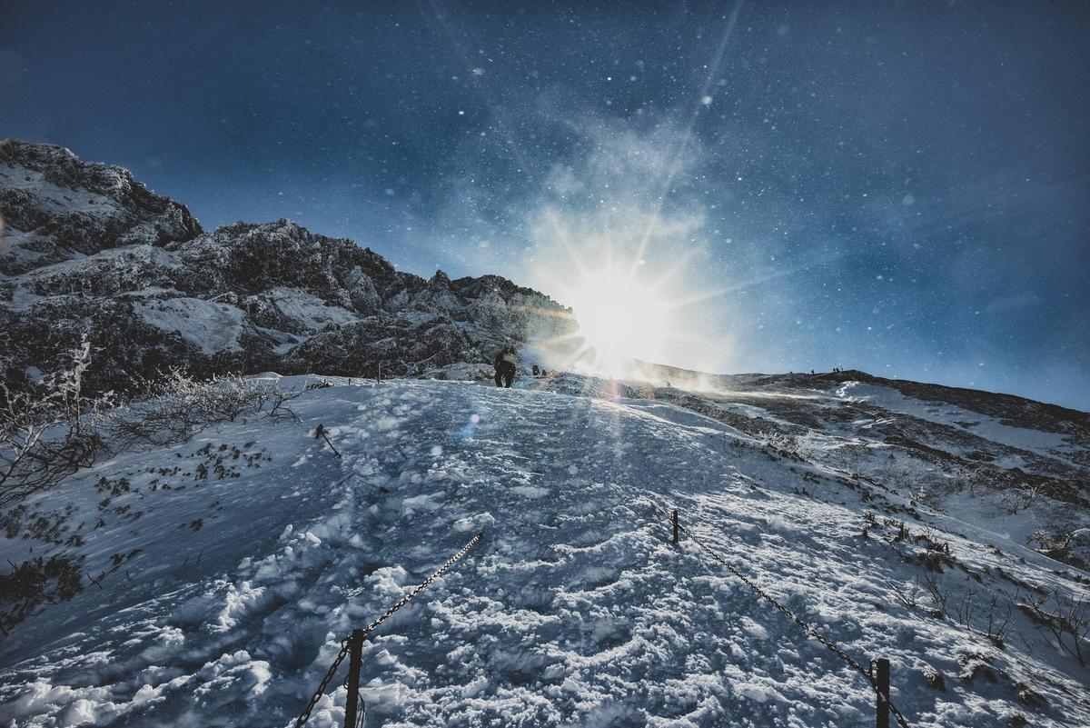 雪煙舞う稜線と登山者のフリー素材(写真)