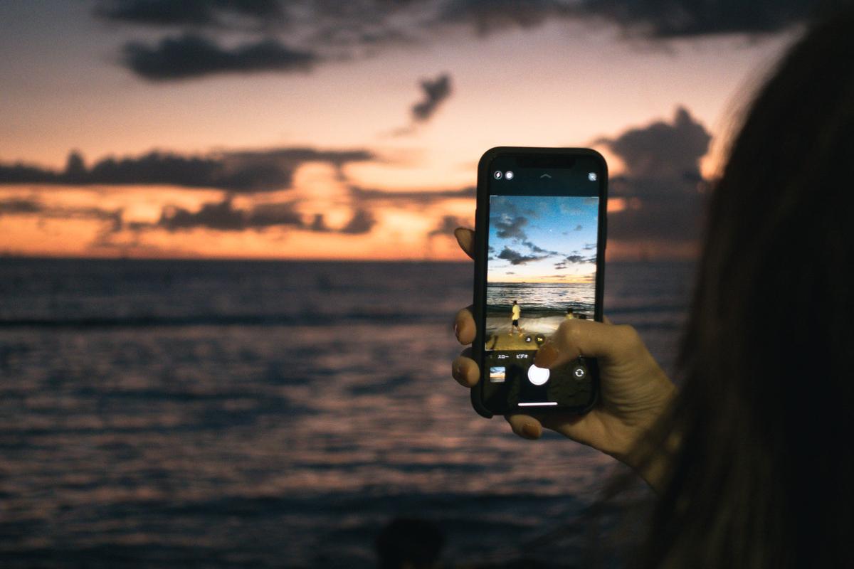 スマホで夕焼けと波打ち際を撮影するのフリー素材(写真)
