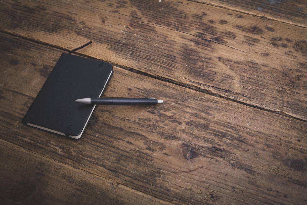 木目のフローリングに置かれた手帳とボールペンの写真素材