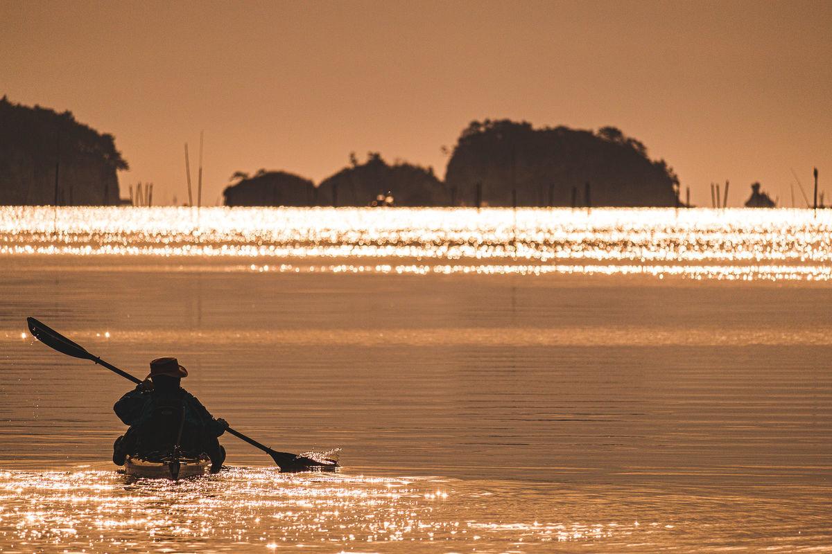 朝日の中を漕ぎ出すカヌーのシルエットの写真素材