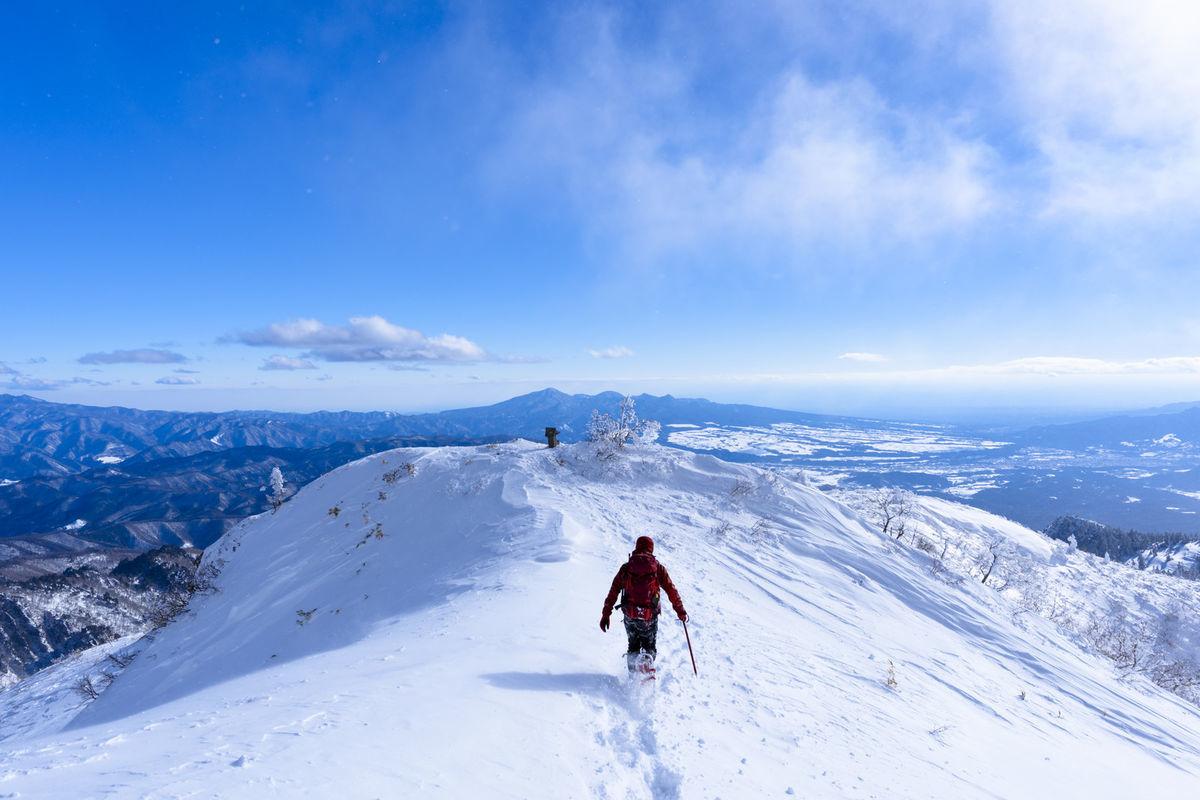 雪原を走る赤い登山者(上州武尊山)の写真素材