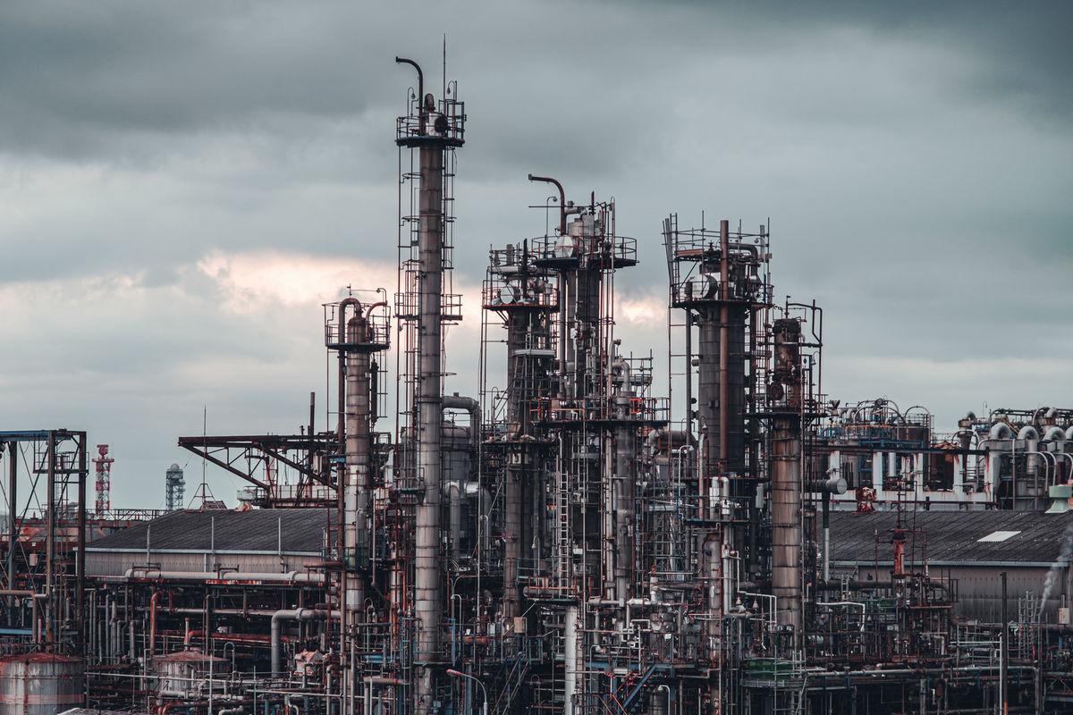 曇り空に並ぶ工場の煙突の写真素材