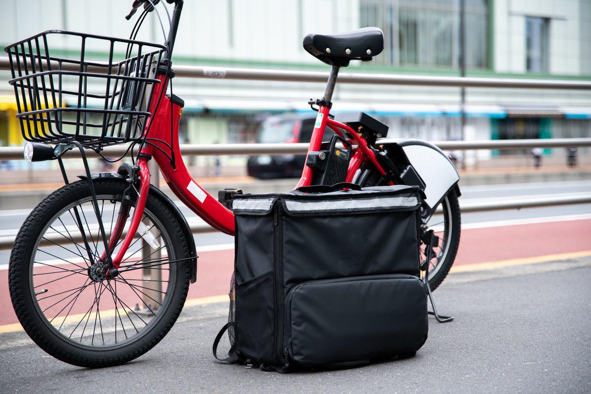 フードデリバリー用のバッグとシェアサイクルの写真素材
