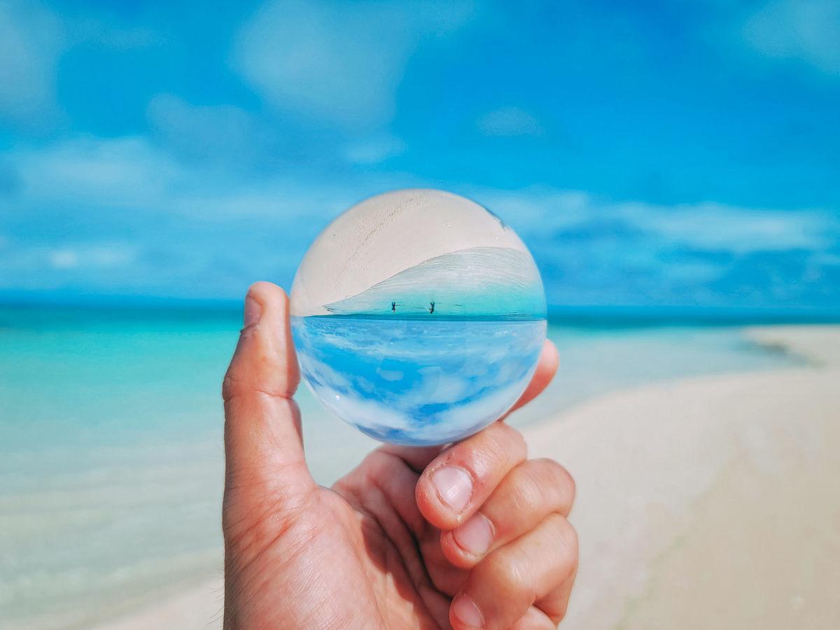 ガラス玉越しに見る南国ビーチの写真素材