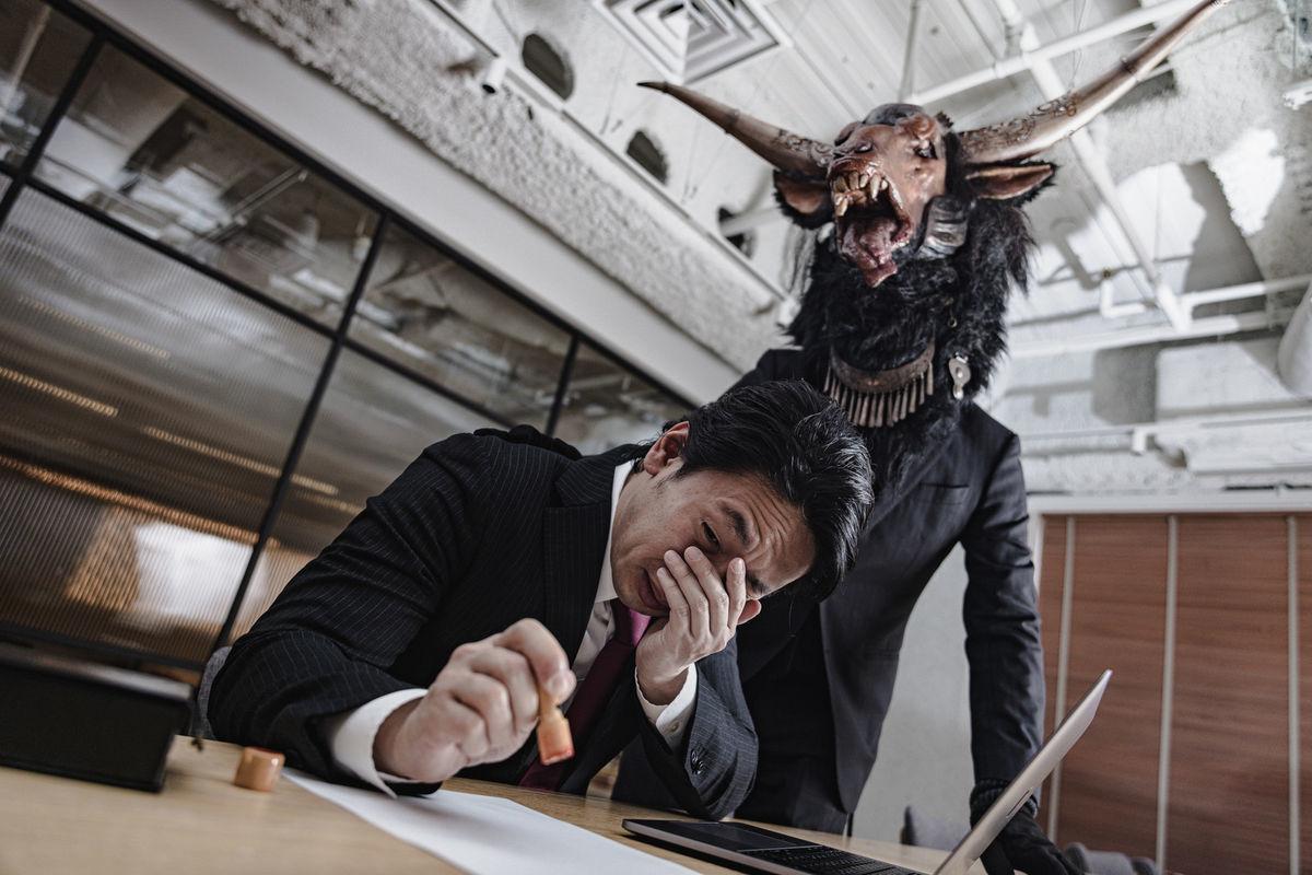 悪魔と契約を結ぶ会社員の写真素材