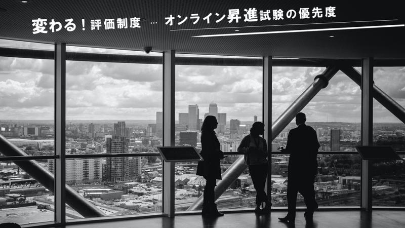 変わる!評価制度…オンライン昇進試験の優先度という文字ば表示されたバナー画像。3人のビジネスパーソンが窓の外を見ている。