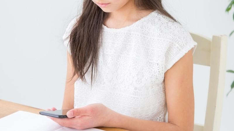 スマートフォンで授業を受けている生徒の画像