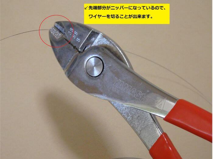 ハンドプレッサーのカッター部分でワイヤーハリスを切っている写真