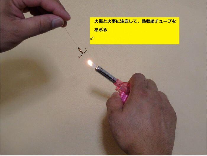 ライターであぶり熱収縮チューブを収縮させハリを固定している写真