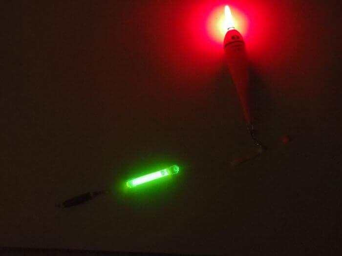 ケミカルライトと電気ウキが暗闇で光っている写真