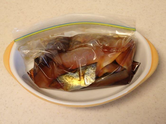 アジとつけ汁を入れた袋をお皿の上に置いた写真