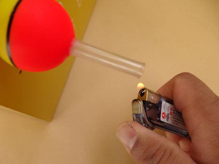 玉ウキにつけたチューブをライターであぶっている写真
